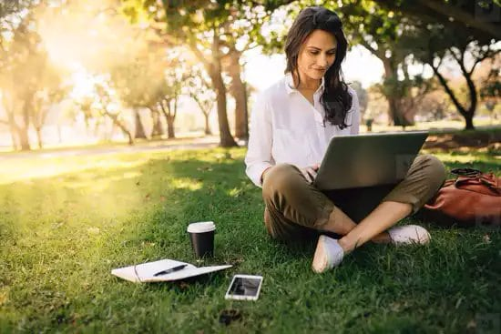 Mujer usando notebook al aire libre